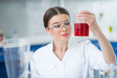 Smiling woman scientist in protective workwear holding flask with reagent Stock Photos