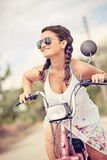 Smiling woman on scooter with sunglasses and braid hair Stock Photography