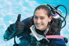 Smiling woman on scuba training in swimming pool showing thumbs up. On a sunny day Stock Photo