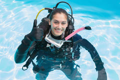 Smiling woman on scuba training in swimming pool showing thumbs up Royalty Free Stock Photo