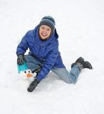 Smiling woman sculpts snowman Stock Photography