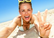 Smiling woman on seacoast taking selfie and showing victory Royalty Free Stock Photo