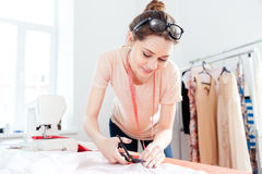 Smiling woman seamstress cutting white fabric with scissors Royalty Free Stock Photo