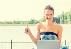 Smiling woman at seaside sitting on grass with computer royalty free stock image