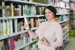 Smiling woman selecting hair care products. In shop and smiling royalty free stock photo