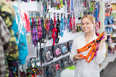 Smiling woman seller  advising on leashes for pets Royalty Free Stock Photography