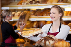 Smiling woman selling cake Royalty Free Stock Photo