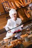 Smiling woman selling fresh pastry and loaves. Beautiful woman selling fresh pastry and loaves in bread section and smiling stock images