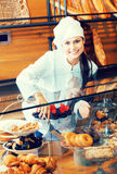 Smiling woman selling fresh pastry and loaves. Pretty woman selling fresh pastry and loaves in bread section and smiling stock image