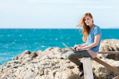 Smiling woman sending emails at the seaside Stock Photo