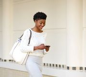 Smiling woman sending text message on mobile phone Royalty Free Stock Image