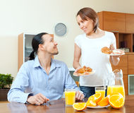 Smiling woman serves breakfast her  husband Stock Photography