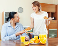 Smiling woman serves croissants and scrambled eggs her  man Royalty Free Stock Images