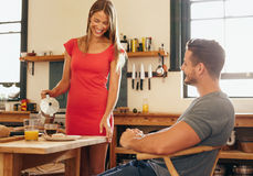 Smiling woman serving breakfast to her boyfriend Royalty Free Stock Photos