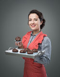 Smiling woman serving chocolate muffins Stock Image