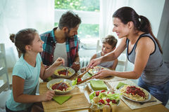 Smiling woman serving meal to her family Stock Photos