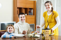 Smiling woman serving soup her husband and child Royalty Free Stock Image