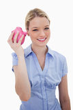Smiling woman shaking her piggy bank Stock Photos