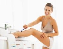 Smiling woman shaving legs in bathroom Royalty Free Stock Image