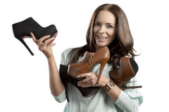 Smiling woman with shoes assortment Royalty Free Stock Photography