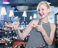 Smiling woman shopaholic holding desired shoe Royalty Free Stock Photo