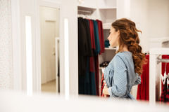Smiling woman shopper in blue dress choosing clothes Royalty Free Stock Photo