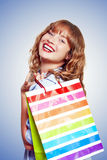 Smiling Woman With Shopping Bag. Beautiful smiling woman holding colourful striped shopping bag over shoulder filled with vitality after a day of shopping in a Stock Photo