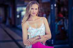 Smiling woman with shopping bag and arms crossed Stock Photography