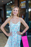 Smiling woman with shopping bag and hands on hips Royalty Free Stock Photos