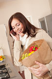 Smiling woman with shopping bag in kitchen Stock Photo