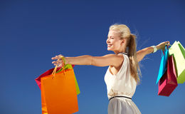Smiling woman with shopping bag rising hands Stock Photography