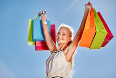 Smiling woman with shopping bag rising hands Royalty Free Stock Photo