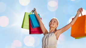 Smiling woman with shopping bag rising hands Stock Images