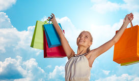 Smiling woman with shopping bag rising hands Royalty Free Stock Photos