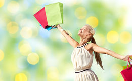 Smiling woman with shopping bag rising hands Stock Photos