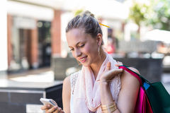Smiling woman with shopping bags calling with mobile phone Stock Photos