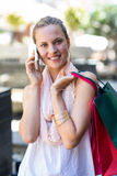 Smiling woman with shopping bags calling with mobile phone Stock Images