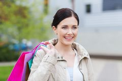 Smiling woman with shopping bags coming from sale Stock Photography