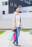 Smiling woman with shopping bags coming from sale Royalty Free Stock Image