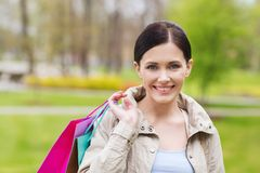 Smiling woman with shopping bags coming from sale Stock Photos
