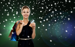 Smiling woman with shopping bags and credit card Royalty Free Stock Images