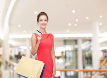 Smiling woman with shopping bags and credit card Royalty Free Stock Photography