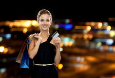Smiling woman with shopping bags and credit card Stock Images