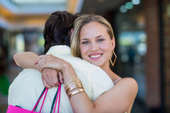Smiling woman with shopping bags hugging her boyfriend Stock Photo