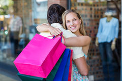 Smiling woman with shopping bags hugging her boyfriend Royalty Free Stock Photography