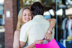 Smiling woman with shopping bags hugging her boyfriend Royalty Free Stock Photos