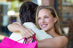 Smiling woman with shopping bags hugging her boyfriend Stock Images