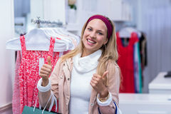Smiling woman with shopping bags looking at camera with thumbs up Royalty Free Stock Images