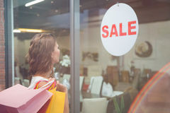 Smiling woman with shopping bags looking at window Royalty Free Stock Image