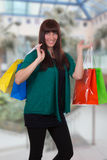 Smiling woman with shopping bags in a mall Stock Photography